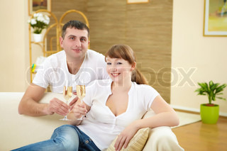 husband and wife celebrating something at home with glasses of chamagne