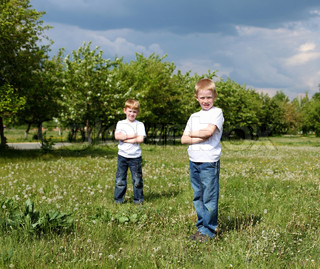 two twin brothers outdoors on the grass