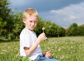 red-hair boy with dandelion in the park