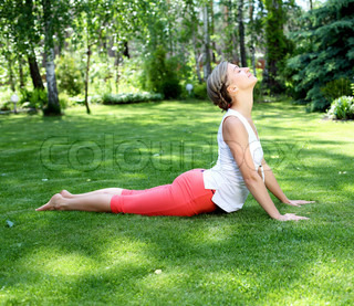 Young girl in a white shirt and red pants doing yoga outdoors