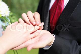 erschossen Sie Moment, wenn der Bräutigam den Ring auf eine junge Braut Hand setzt,