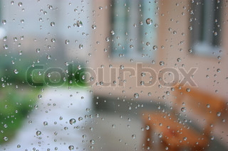 Picture through glass with drops after the rain On a background the house and a bench