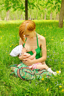 Mother feeding her baby with breast outdoor shot