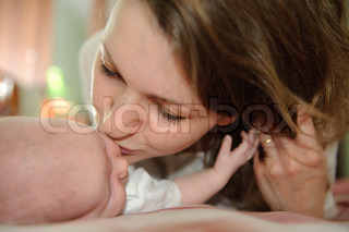 Young mother is kissing her little baby
