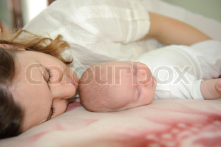 Young mother is sleeping with her little baby