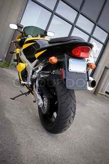 The rear view of a modern yellow motorcycle