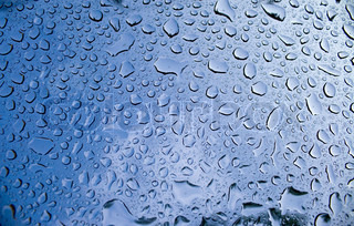 A macro of some beautiful water droplets over a blue background