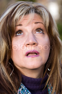 A pretty middle aged woman looking upwards in confusion