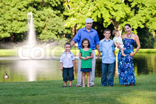 An attractive young family together at the park together on a nice spring or summer day