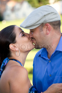 A young couple kissing each other on the lips