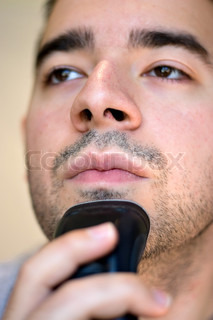 A closeup of a young man shaving his beard off with an electric shaver Shallow depth of field