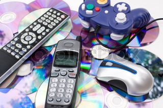 Remote control wireless computer mouse cordless telephone and video game controller over a bed of dvd disks isolated over white