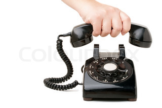 holding the handset of an old black vintage rotary style telephone isolated over white