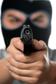 An angry looking man wearing a ski mask pointing a black handgun at the viewer Works great for crime or home security concepts