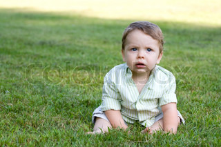 Cute young infant sitting in the grass all alone