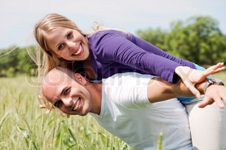 Happy couple enjoying with their arms outstreched in the park