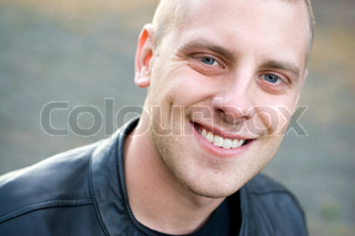 Closeup of the face of a happy young man with a big smile
