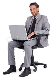 Business man sitting with laptop and smiling at office desk isolated white background