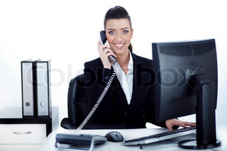 Smiling woman busy over phone at office