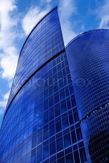 Modern skyscrapers close-up under blue sky with clouds