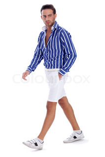 Young guy in casual wear walking with one hand in his pocket