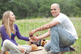 Couple sitting in blanket smiling with picnic mode on green grass