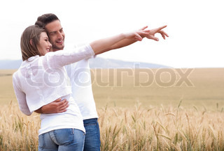 Young couple in meadow pointing in the air, hugging in the park