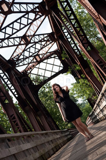 A carefree brunette woman walking along an old rusted bridge