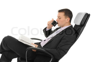 Businessman reading a book and drinking coffee sitting in a chair in a bright office Isolated on white background