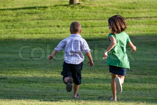 A little boy and girl run through the grassy field without a care in the world