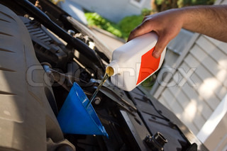 A backyard mechanic pours motor oil into the engine at the end of an oil changeHome maintenance is becoming more popular during hard economic times