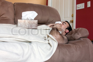 A young adult sick on the couch at home blows his nose with a tissue