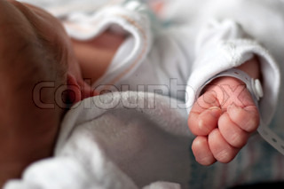 Close up of a newborn infants baby hand and wristband shortly after birth Shallow depth of field
