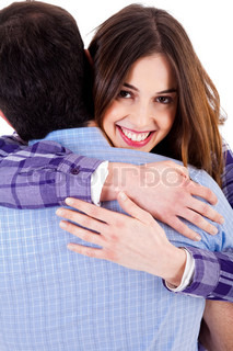 closeup of smiling young woman hugging man and looking at camera
