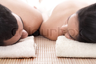 Young man and woman lying on towel to take spa in isolated background