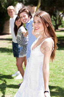 Four teens hang out in a park as they join hands while standing together in a row
