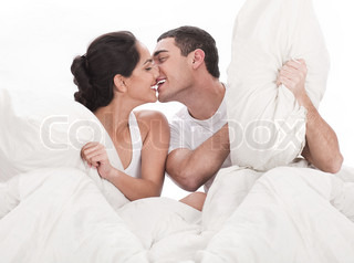 Couple kissing and playing on bed in bedroom, in passion over white background