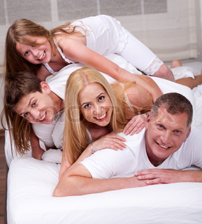 Cheerful family having fun together lying on a bed in living room