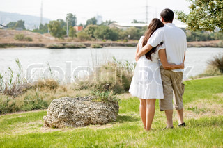 Rear view full section of couple holding eachother in green field