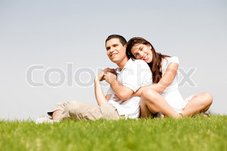 Happy young women with arms around her husband and laying on his shoulder in a park