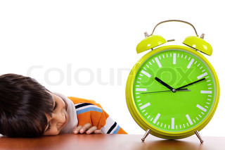 Boy tired of study and sleeping near the clock