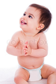 Beautiful toddler clapping is hands and looking the right corner in a white background