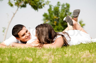 happy young Couple lie down on grass look each other