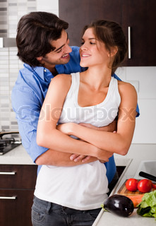 husband hold her wife and about to kiss in their kitchen