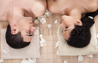 Lovely couple looking eachother during spa treatment in white background