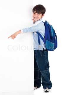 Young kid happily standing behind the board and pointing to empty space on white isolated background