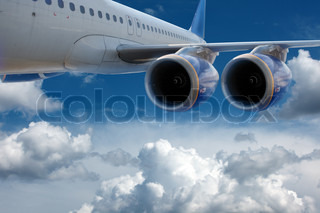 Big airliner in the blue sky with clouds
