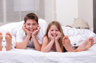 Loving Brother and sister lying and having fun on the bed looking at you