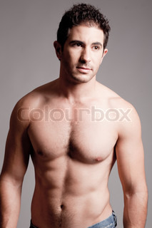 Fit man showing chest and abs on a grey background
