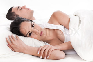 Couple in bed, men sleeping and woman lying sleepless in white background